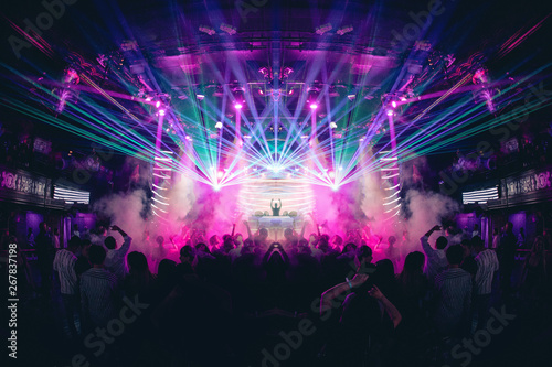 DJ with Hands up in a Nightclub with Lasers Fototapeta