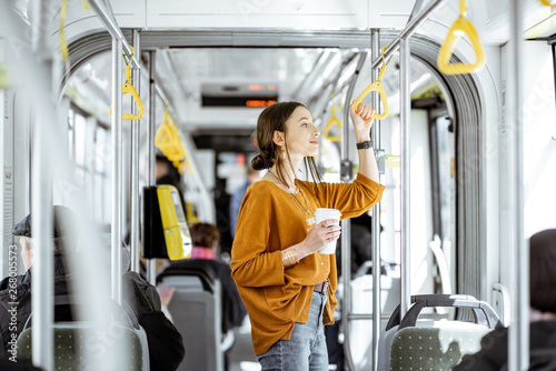 Tela Young woman passenger enjoying trip at the public transport, standing with coffe