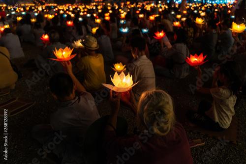 Wallpaper Mural Buddhist hold lanterns and garlands praying at night on Vesak day for celebratin