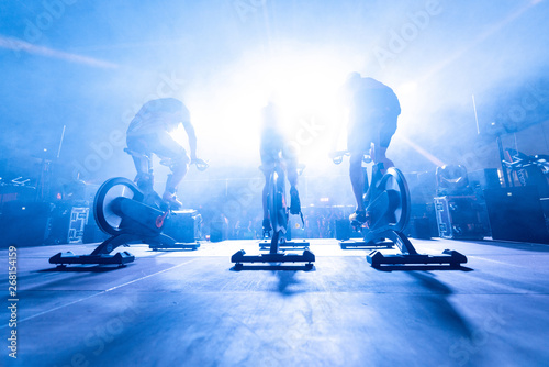 Fotografie, Obraz spinning instructors on stage,  before a group of people doing spinning on cycle