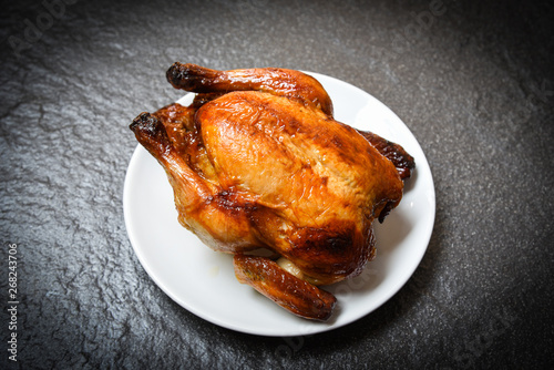 Fotografia Roasted chicken - baked whole chicken grilled on white plate and dark background