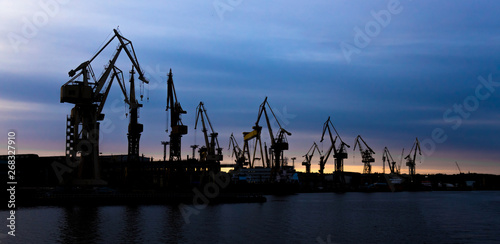 View on a shipyard with cranes at the sunset. Fototapet