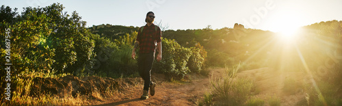 Photo bearded millennial hiker walking trail with backpack during sunset