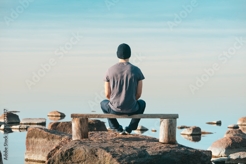 Fototapeta A man sits on a wooden bench and admires the complete calm of the sea