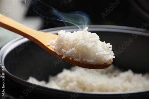 Obraz na plátně Spoon with tasty hot rice over cooker, closeup