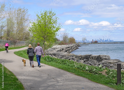 Photo A couple walks a dog as a cyclist rides by on Toronto's waterfront trail route b