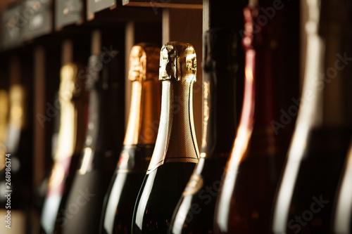 Photo Underground cellar with elite sparkling wine on shelves, close up horizontal photo
