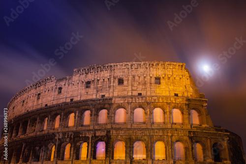 Photo Dettaglio del Colosseo di notte con la luna piena in lunga esposizione  e finest