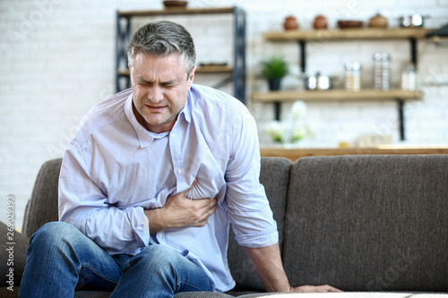 Handsome mature man having heart attack at home Fototapet