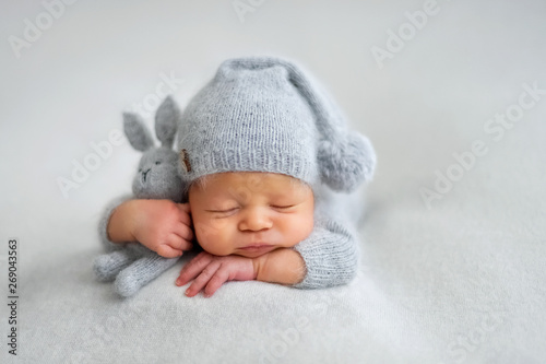 Fotografia Sleeping newborn boy in the first days of life on white background