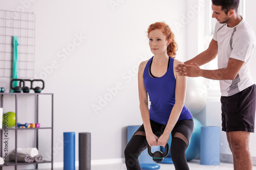 Professional personal trainer supporting sportswoman exercising with weight Fototapeta
