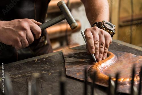 Fotomural a blacksmith makes a piece of bronze