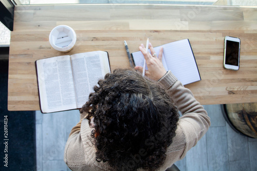 Stampa su Tela top view of black woman making notes while studying her bible
