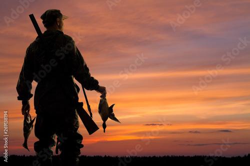 Fototapeta duck hunter with prey at sunset