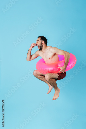 Fotografie, Obraz Photo of attractive shirtless tourist man wearing rubber ring smiling while swim