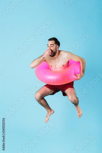 Fotografie, Tablou Photo of joyful shirtless tourist man wearing rubber ring smiling while swimming