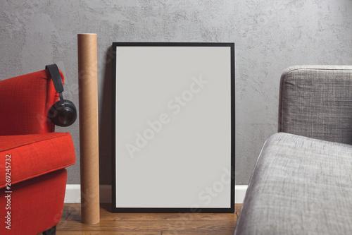 Ramka na plakat stoi oparta o betonową ścianę na drewnianej podłodze w salonie, obok niej stoi czerwony fotel, leżą także słuchawki.