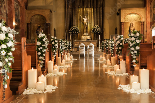 Catholic temple decorated with flowers and candles for wedding Fototapeta