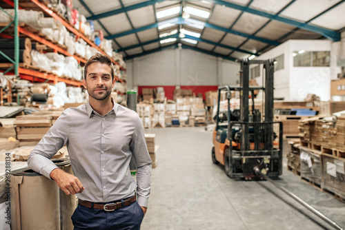 Smiling manager leaning against stock in a large warehouse Fototapet