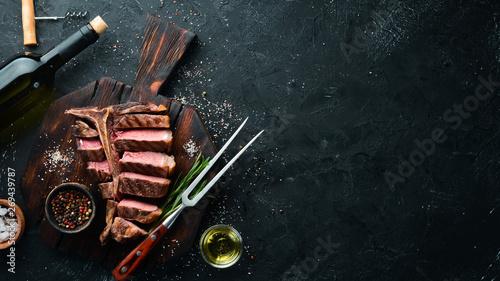 Foto Beef T-Bone steak on a black table