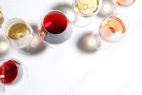 Fototapeta Different glasses with wine on white background, top view