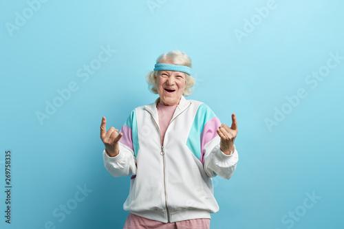Fotografia, Obraz Cute hipster grandmother smiling and making rock sign against blue studio backgr