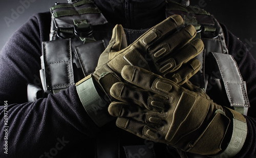 Canvas Print Warrior soldier in tactical gloves standing front view closeup.