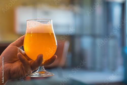 Fototapeta man holds in his hand a glass of craft beer