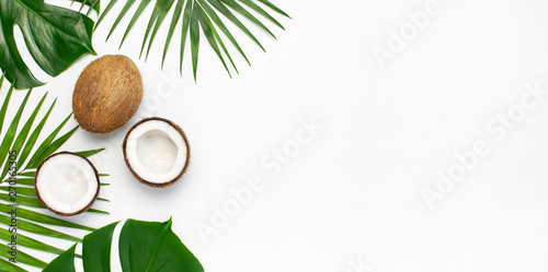 Foto Tropical leaves and fresh coconut on light gray background