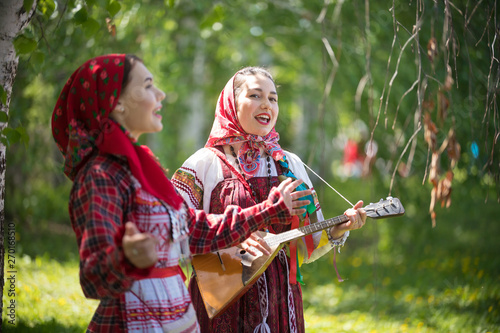 Photo Two young woman in traditional russian clothes singing in the forest
