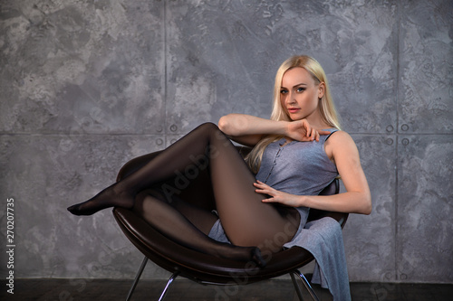 Photo Beautiful blonde girl in pantyhose posing in the chair.