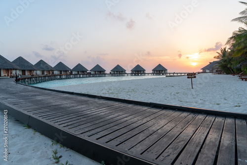 Fotografie, Obraz curvy plank with water villas at the beach during sunset