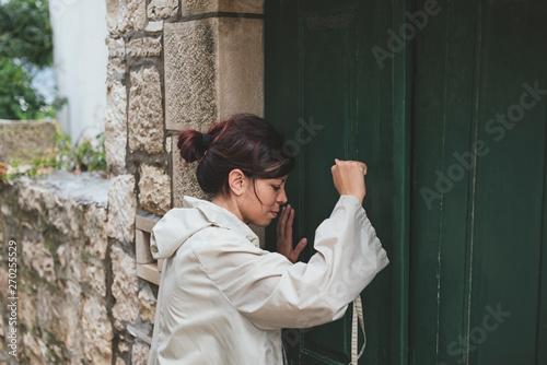 Girl in a raincoat in front of the green door Fototapete