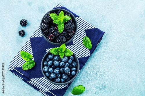 Slika na platnu Frische Blaubeeren und Brombeeren auf blauem Hintergrund