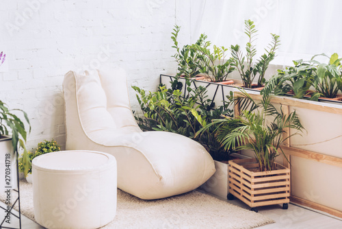 Slika na platnu white soft chaise lounge and pouf in room with lush green plants