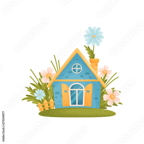 Foto Fabulous blue house with a sharp roof among the flowers
