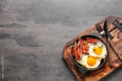 Slika na platnu Frying pan with tasty eggs and bacon on grey background