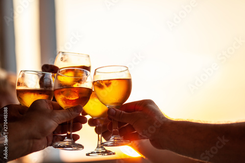 фотография Close-up shot of friends or family raising glasses and toasting with wine agains