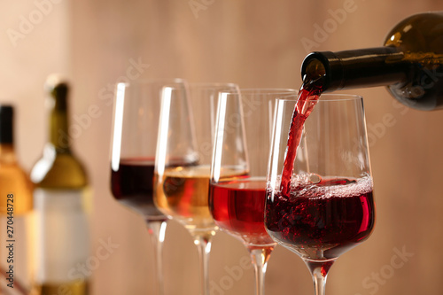 Fotografia, Obraz Pouring wine from bottle into glass on blurred background, closeup