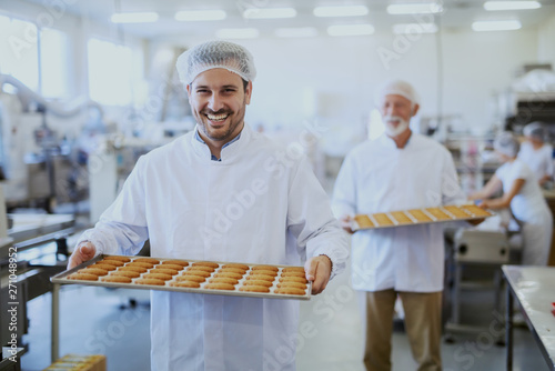 Obraz na płótnie Food plant workers in sterile uniforms carrying trays with cookies