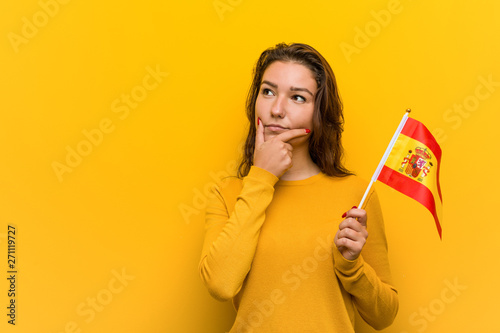 Wallpaper Mural Young european woman holding a spanish flag looking sideways with doubtful and skeptical expression