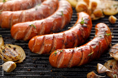 Fotografia Grilling sausages with the addition of herbs and vegetables on the grill plate, close-up