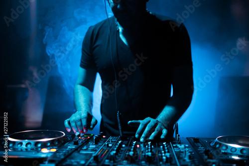 Fotografia DJ mixing tracks on a mixer in a nightclub
