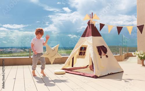 Obraz na płótnie happy young boy, kid playing near the textile wigwam tent on the summer patio