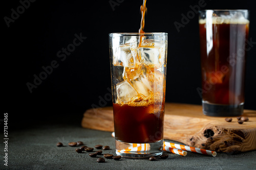 Stampa su Tela Ice coffee in a tall glass with cream poured over, ice cubes and beans on a old rustic wooden table