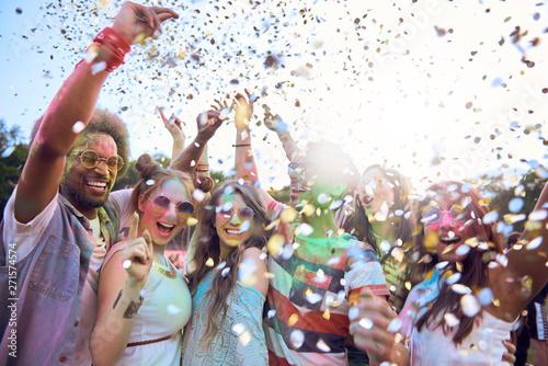 Friends celebrating holi festival under shower of confetti Fototapeta