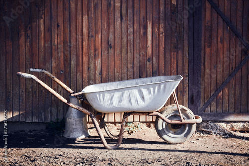 Photographie Vintage white empty wheelbarrow against the wooden wall of a barn