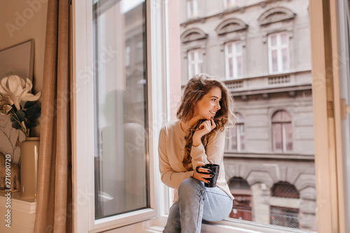 Carta da parati Romantic female model in good mood looking at street, sitting on sill