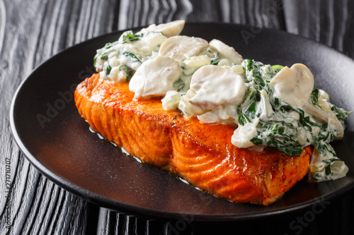 Photo Baked Florentine salmon with creamy wine sauce, seasoned with roasted spinach and mushrooms closeup on a plate