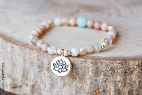 Fotomural Mineral stone sun stone and lotus pendant bead bracelet on natural wooden backgr